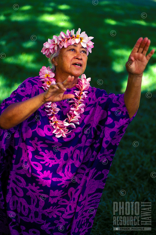 Auntie dancing an auana ( modern) hula with plumeria leis