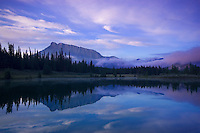 Sunrise at the cascade ponds in Banff with Mt Rundle in the background as storm clouds roll out