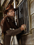 Cowboy standing at a barred window, attempting to rob a bank at night