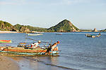 Two fishermen haul their boat into the water on the Kuta beach, Lombok, Indonesia.