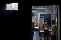 Women chat outside a traditional kitchen of an old house in the ancient Huangxi village of Dali in Foshan city, Guangdong province, November 11, 2011.