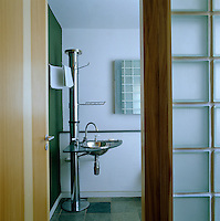 A small hand basin is cantilevered off a chrome column whch also includes a towel rail and soap rack
