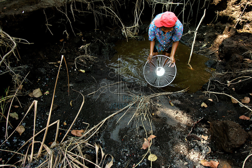 A boy catches shrimp for fun in a hole left weeks earlier by the Chiguate River. Torrential rains associated with Hurricane Stan inundated parts of Central America in early October, causing flooding, mudslides and death across western Guatemala. Contamination from mud and chemicals from upstream killed the large fish in the river, locals said, and shrimp are the only food source in it now.<br />