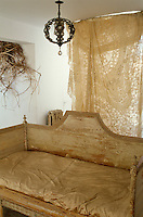 A distressed Louis XVI canape in the living room is covered in gold satin with a length of antique lace hanging as a curtain behind