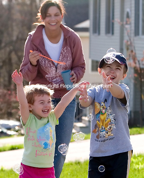 WATERBURY, CT- 30 APRIL 07- 043007JT01-<br /> Siblings Katie and Joseph Noga, of Oakville, chase bubbles blown by their cousin, Valerie Bartley, as they play outside in front of their grandmother's house off of Oronoke Road in Waterbury on Monday afternoon.<br /> Josalee Thrift Republican-American