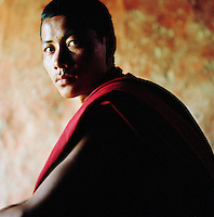 Portrait of young monk sat in doorway of monastery, Ladakh, India