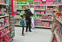 NWA Media/Michael Woods --12/06/2014-- w @NWAMICHAELW...Corporal Shawn Allen with the Fayetteville Police Department helps Shakhia Cheers, age 6 from Fayetteville, pick out a toy Saturday morning during the shop with a cop event at Walmart on MLK Blvd in Fayetteville.  Several local law enforcement agencies participating in the annual event to help local children, the Fayetteville police department help out about 100 local children during the event.