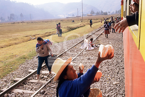 Machu Pichu Railway, Peru. Woman in traditional clothes selling bread for people travelling on the train.