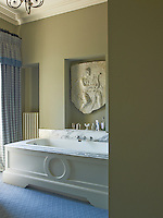 A plaster cast bought in an antique shop in Notting Hill has been placed above the bath in this blue themed bathroom