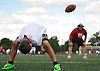 Joey Diesso, 9, of Massapequa works on long snaps with Mike Dimitriou, head coach of Floral Park junior varsity football, during the Long Island Youth Football Player Academy at Cedar Creek Park in Seaford on Monday, July 11, 2016.