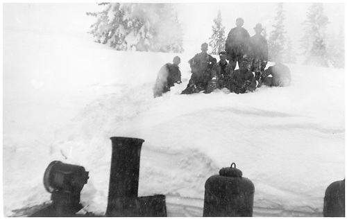 Woekmen posing for photo on large snowdrift with topmost portion of an engine below.<br /> D&amp;RG  Cumbres Pass ?, CO