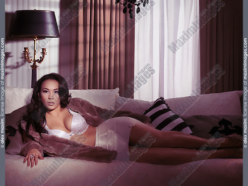 Glamour photo of a young woman wearing lingerie and fur coat lying on a sofa in front of a window