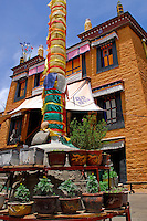 Courtyard of Ani Sanghkhung Nunnery with darchen, or prayer flag pole, mani, or prayer, stone carved with mantra Om Mani Padme Hum, and painted windows, rooftop prayer flags, victory banners on the main chapel, Lhasa, Tibet, China.