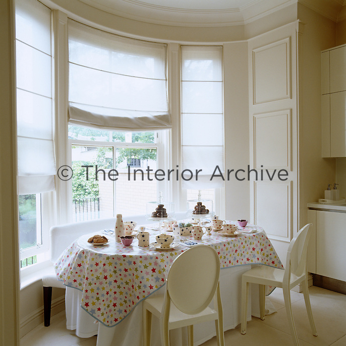 A table is laid for tea with an Emma Bridgewater service in the bay window of the breakfast room