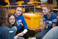 Salve Regina volunteers Cathryn Blair,'18, right, and Genna Hoyt,'18, help Keira Foster and Julia Connelly with their language skills at the Pell School in Newport.