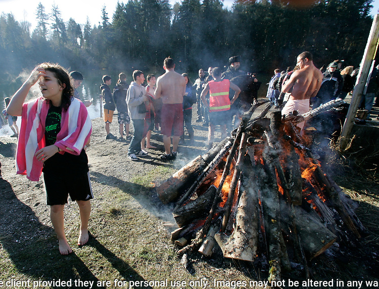 After jumping into the icy waters of the Olalla Lagoon, Shanna Gregory,  warms up near a fire in Olalla, Washington on January 1, 2011. Over 300 hardy participants  braved the chilly lagoon waters to join in on the annual New Year's Day Tradition. ©2011. Jim Bryant. All Rights Reserved.