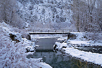 A winter scene of Billy Creek Bridge spanning the Uncompahgre River and surrounding landscape covered in snow. Colorado.