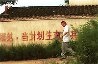 A man passes a sign that telling people to be responsible and respect the One Child Policy in Caidian village.<br /> ©sinopix