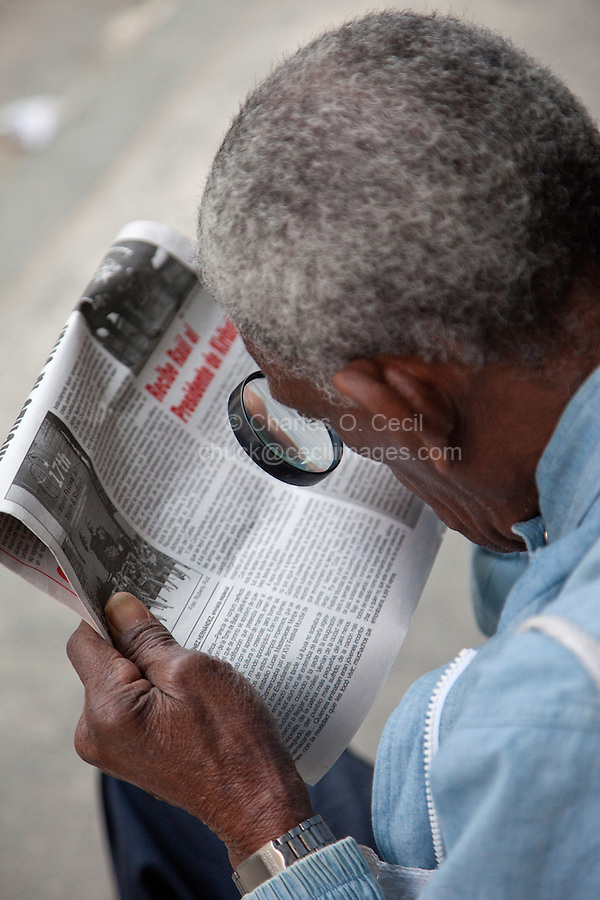 Cuba, Havana.  Man Using Magnifying Glass to Read Granma, the Official Party Newspaper.