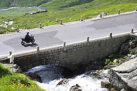Biker on bridge over Alpine spring