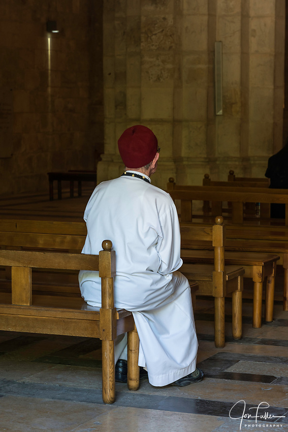 A Catholic priest of the Order of the Missionaries of Africa, also known as the White Fathers, in the Church of Saint Anne in the Muslim Quarter of the Old City of Jerusalem.  The Old City of Jerusalem and its Walls is a UNESCO World Heritage Site.