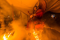 The figure of Holika burning a top a pyre during the Holika Dahan in Mathura on Purnima (full moon) the night before Holi; Mathura, Uttar Pradesh, India.