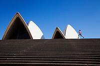 A woman runs along the steps of the Sydney Opera House.  Sydney, New South Wales, AUSTRALIA.