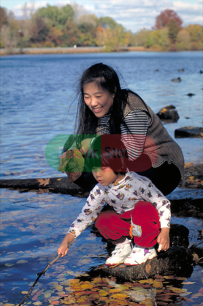 young woman playing with toddler girl with water