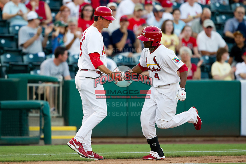 Daryl Jones (4) of the Springfield Cardinals shakes hands with Manager Ron Warner (57) after hitting a home run during a game against the Tulsa Drillers at Hammons Field on July 18, 2011 in Springfield, Missouri. Tulsa defeated Springfield 13-8. (David Welker / Four Seam Images)