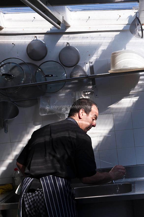 """Antonello Serra, nato ad Oristano nel  1961, si trasferisce a Londra nel 1995 per lavorare come cuoco e per garantire cure adeguate a sua figlia Giorgia. Nel 2006, insieme al cognato Roberto Brai, apre, nel quartiere di Brockley a Londra, il ristorante """"Le Querce"""".  Qui è ritratto mentre lavora in cucina."""