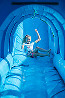 NWA Democrat-Gazette/J.T. WAMPLER Emma Johnson of Littler Rock takes a trip down an inflatable water slide Sunday July 8, 2018 in downtown Springdale. Johnson competed in the Natural State Criterium Series bicycle race, coming in second overall in her race. Sunday was the last day of the third annual race series that included events in downtown Bentonville and Rogers as well.