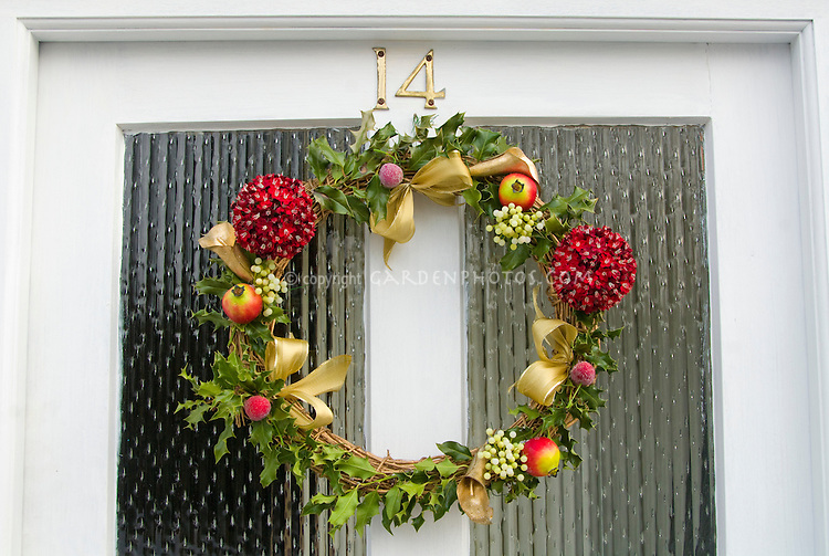 Winter holiday wreath on front house door for Christmas trim holiday decorating, curb appeal welcome