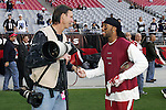 Retired Major League Baseball player Randy Johnson becomes a photographer and works the the NFL sidelines here talking with Larry Fitzgerald before a game between the Arizona Cardinals and the Dallas Cowboys at University of Phoenix Stadium in Glendale, AZ on 12/4/11.