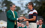Billy Payne presents Oliver Goss with the low amateur trophy after the final round of the Masters Tournament at Augusta National Golf Club Sunday, April 13, 2014, in Augusta, Ga.