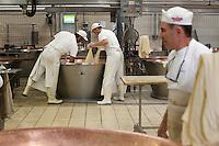 Fiorenzuola: lavorazione della produzione del Grana Padano nell'azienda Colla...Fiorenzuola: men work for the production of Grana Padano in the farm Colla