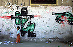 "A mural showing a Palestinian fighter shooting an RPG rocket to an Israeli tank is seen in the ""Beach refugee camp"", in Gaza strip, June 9, 2004. Photo by Quique Kierszenbaum"