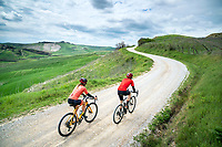 Cyclists riding gravel on the famous Strade Bianche out of Pienza, in Tuscany, Italy