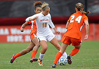 COLLEGE PARK, MD - OCTOBER 28, 2012:  Riley Barger (10) of the University of Maryland controls the ball between Jasmine Paterson (15) and Tara Schwitter (24) of Miami during an ACC  women's tournament 1st. round match at Ludwig Field in College Park, MD. on October 28. Maryland won 2-1 on a golden goal in extra time.