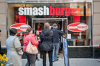 Burger lovers from far and wide descend on the new Smashburger restaurant in the shadow of the Empire State Building in New York on its grand opening day, Thursday, April 10, 2014. The popular Colorado chain, which has a cultish following, opened its first Manhattan outpost  bringing their burgers, smashed to order to the Big Apple. The fast casual restaurant has a loyal fan base and has 260 restaurants worldwide. The franchise welcomed their Manhattan customers by offering a free Classic Smashburger to each patron all day, with the line eventually stretching around the block.  (© Richard B. Levine)