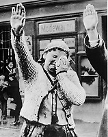 "Title: The tragedy of this Sudeten woman, unable to conceal her misery as she dutifully salutes the triumphant Hitler, is the tragedy of the silent millions who have been ""won over"" to Hitlerism by the ""everlasting use"" of ruthless force., ca. 1938"
