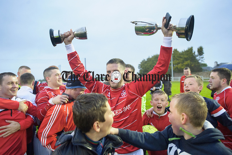 Captain of Newmarket Celtic Eoin O Brien shows the players the cup following the win over Bridge United in their Cup final at Doora. Photograph by John Kelly.