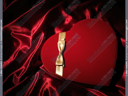Red heart-shaped gift box with a golden bow