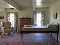 A guest bedroom is furnished with an early 19th-century Sheridan bed and a Connecticut tall chest