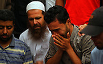 A Palestinian mourner cries at a mosque as he sits next to the bodies of Mousa Abu Muamer, 56, and his son Saddam, 27, who were killed in an overnight Israeli missile strike at their house in the outskirts of the town of Khan Younis, southern Gaza Strip, Monday, July 14, 2014. Saddam's wife, Hanadi, 27, was also killed in the attack. Photo by Ramadan El-Agha