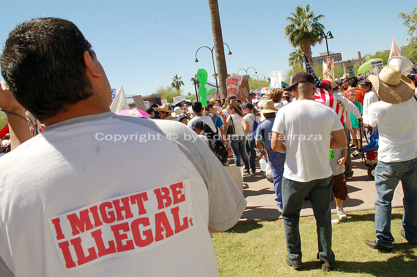 "Phoenix, Arizona. May 29, 2010 - Thousands of demonstrators participated in a pro-immigration reform rally and march to protest the recent enactment of Arizona controversial immigration law SB 1070, also known as the ""Show Me Your Papers"" law. People gathered at Steele Indian Park and marched from there to the Arizona State Capitol. This scene shows a man wearing a sign on the back of his T-shirt that reads ""I Might Be Illegal,"" in reference to the practice of racial profiling critics of the SB 1070 law say will cause once it is put into effect. Since the massive immigration demonstrations in 2006, Arizona has been called ""ground zero"" of the immigration debate, mainly due to legislation approved to fight illegal immigration in the state. Photo by Eduardo Barraza © 2010"