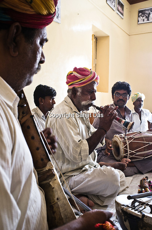 66-year-old Manganiyar artist, Pempa Khan plays his Murli (wind instrument) while Ghewar Khan (45, Left) and Firoze Khan (38, right) accompany him during field recordings inside their house in Hamira village of Jaiselmer district in Rajasthan, India. Photo: Sanjit Das/Panos