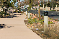 A long view down the Harbor Boulevard Cornerstone Bike Trail in Costa Mesa, California under a clear blue sky.  This long view has less sky and more pathway visible than the other, similar image.  The landscaping of the path, including a diversity of plants and rocks, can be seen, as can the street and many light posts.  The landscape architecture work on the project was done by David Volz Design.
