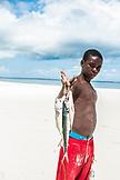ZANZIBAR, Nungwi Beach,  a Boy is holding three fish, ocean in the background