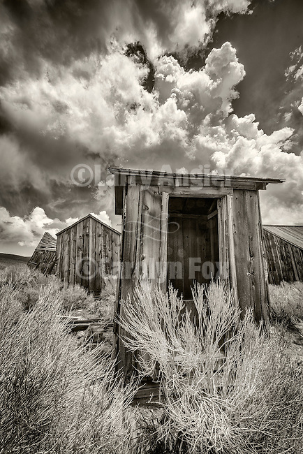 Leaning outhouse and clouds, the ghost town of Bodie, California, State Historic Park.