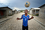 "A boy bounces a football on his head in a model resettlement village constructed by the Lutheran World Federation in Gressier, Haiti. The settlement houses 150 families who were left homeless by the 2010 earthquake, and represents an intentional effort to ""build back better,"" creating a sustainable and democratic community."